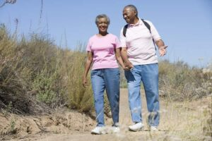 Photo of happy healthy African American senior couple on walking trail from