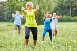 Photo of Seniors doing Qi Gong or Tai Chi exercise in nature from