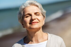 Photo of mature woman smiling with eyes closed towards the sun from