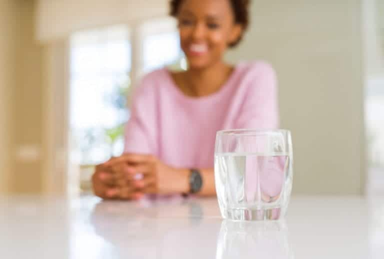 """Photo of glass of clean water on table with African American woman smiling in background from """"3-Day Water Fasting vs. 3-Day Modified Fasting"""" by Green Smoothie Girl"""