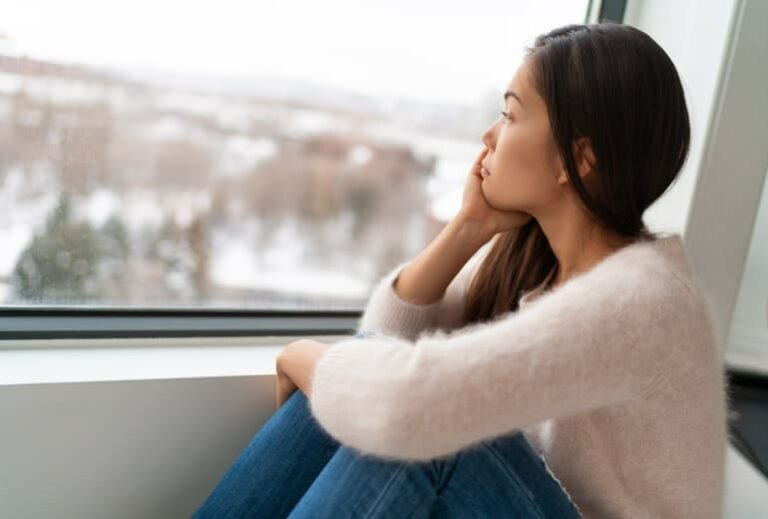 "Photo of sad Asian woman looking out window from ""10 Green Smoothies For Seasonal Affective Disorder"" by Green Smoothie Girl"