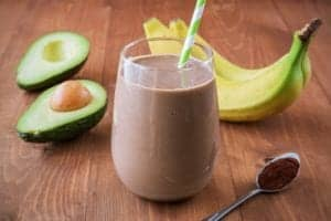 Photo of chocolate brown Muddy Buddy green smoothie with striped straw inserted and bananas and avocados surrounding it from