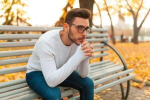 Photo of young man wearing glasses with sad expression sitting on park bench with yellow autumn leaves around from