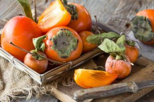 Photo of fresh whole and cut persimmons on wooden board with knife from