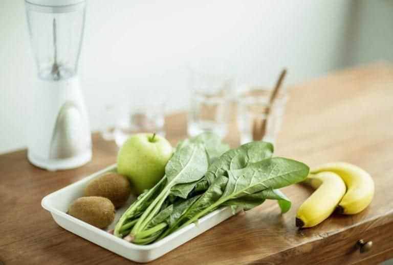 "Photo of spinach, apple, and kiwis in tray on wooden table with blender and glass cups in background from ""15 Tasty Meal Replacement Smoothie Recipes To Fill You Up & Keep You Going"" blog post by Green Smoothie Girl"