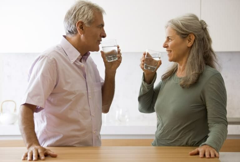 "Photo of mature couple smiling at each other and drinking water in kitchen from ""9 Tips For Sailing Through a 3-Day Modified Fast"" blog post by Green Smoothie Girl"