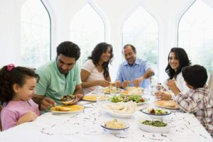 Photo of happy middle-eastern family eating dinner together from