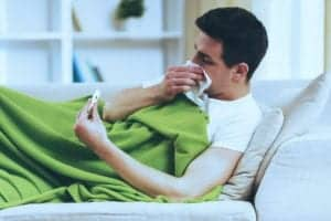 """Photo of man laying on couch under blanket blowing his nose and looking at thermometer from """"10 Green Smoothies To Beat Back Colds And Flu"""" by Green Smoothie Girl"""