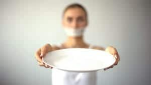 Photo of skinny woman with taped mouth holding up an empty plate from