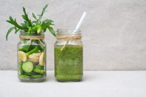 Photo of two mason jars, one with cucumber and banana slices and one with a green smoothie from