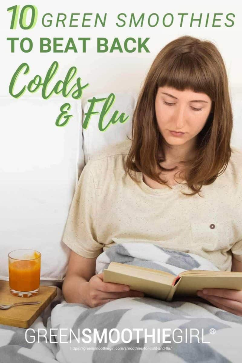 "Photo of brunette woman sitting in bed reading a book with an orange tonic drink beside her and post's title text overlay from ""10 Green Smoothies To Beat Back Colds and Flu"" by Green Smoothie Girl"