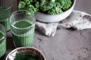 "Photo of three green smoothies and two bowls of kale from ""9 Green Smoothies For Clear, Younger-Looking Skin From The Inside Out"" by Green Smoothie Girl"
