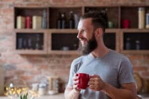 Photo of white man standing in kitchen smiling and holding mug of tea from