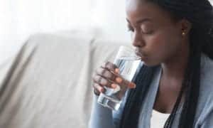 "Photo of African American woman with long hair sitting on couch and drinking clear water from ""How Do I Prepare For a 3-Day Modified Fast?"" blog post by Green Smoothie Girl"