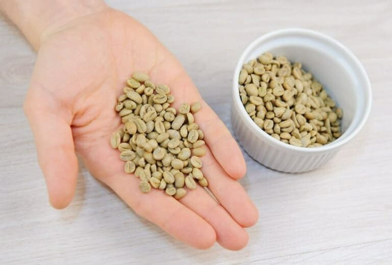 """Photo of person's hand holding unroasted coffee beans in hand from """"Coffee Enemas: Crazy effective, or Just Crazy?"""" blog post from Green Smoothie Girl"""