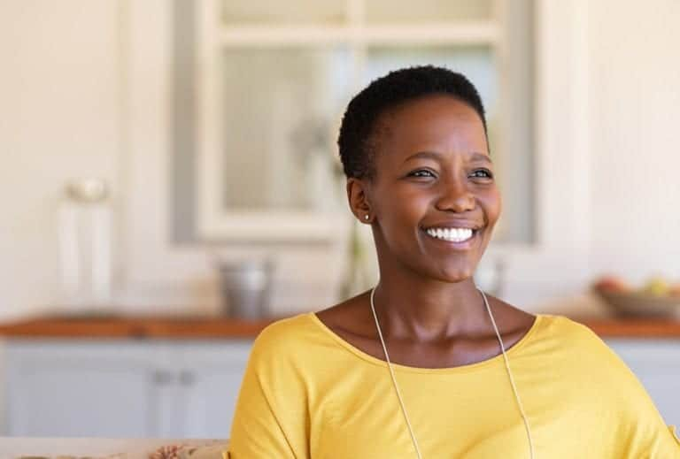 "Photo of smiling African American woman in yellow shirt from ""9 Green Smoothies For Clear, Younger-Looking Skin From The Inside Out"" blog post by Green Smoothie Girl"