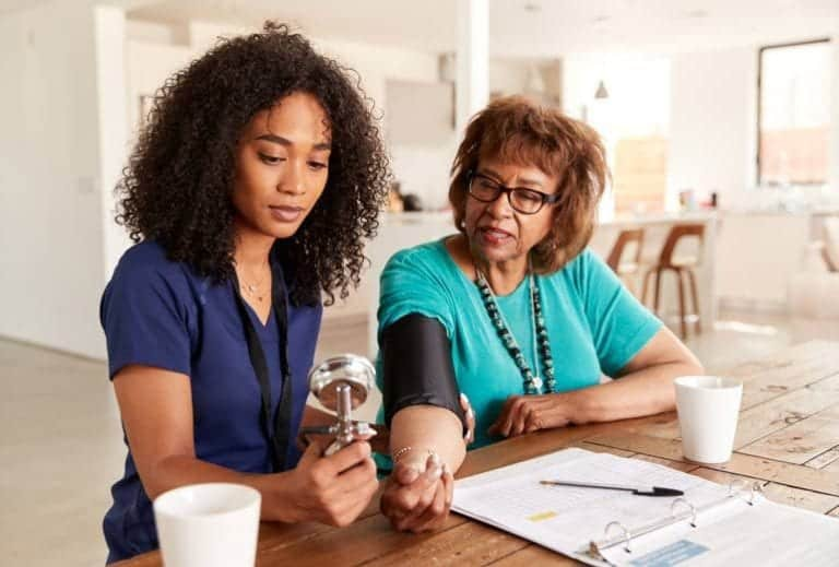 "Photo of African American female nurse helping elderly woman take blood pressure from ""Can Modified Fasting Help Control Blood Pressure?"" by Green Smoothie Girl"