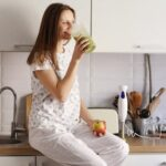 A woman drinking a green smoothie while sitting on the kitchen counter from Green Smoothie Girl
