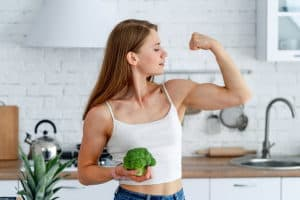 A strong woman flexing her muscles while holding a broccoli in a kitchen.