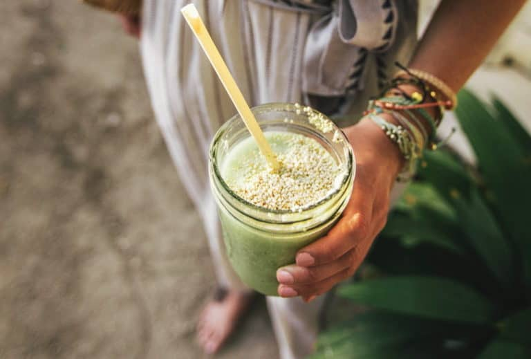 woman holding a green smoothie with a yellow straw in a jar