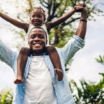 A smiling man holding his smiling daughter on his shoulders outside