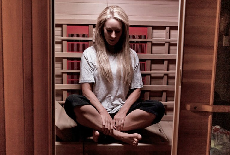 "Robyn sitting in a yoga pose in her sauna from Green Smoothie Girl's ""19 Benefits of Infrared Saunas"""