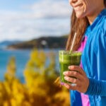 """a woman outside holds a green smoothie from Green Smoothie Girl's """"10 Fall Smoothies"""""""