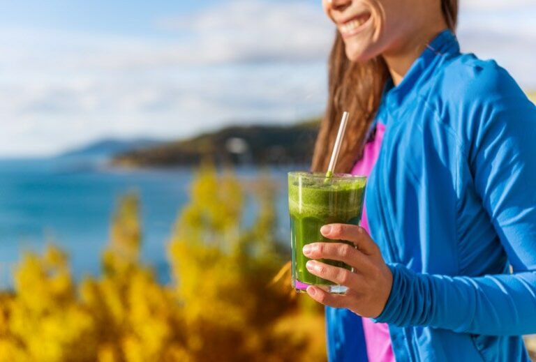 "a woman outside holds a green smoothie from Green Smoothie Girl's ""10 Fall Smoothies"""