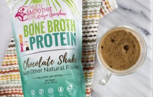 "A bag of Green Smoothie GIrl's Bone Broth Protein next to a clear mug of hot chocolate from Green Smoothie Girl's ""Easy, Gut-Healthy Bone Broth Hot Chocolate"""