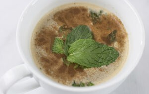 "a steaming mug of coffee with mint leaves in it from Green Smoothie Girl's ""Healthy High-Protein Peppermint Mocha"""