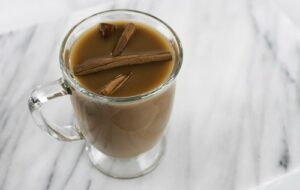 "Hot chocolate with cinnamon sticks in a clear mug from Green Smoothie Girl's ""Morning Chocolate Elixir"""