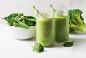 A photo of two green smoothies with green and white straws next to a broccoli floret and a white bowl of spinach with a white background.