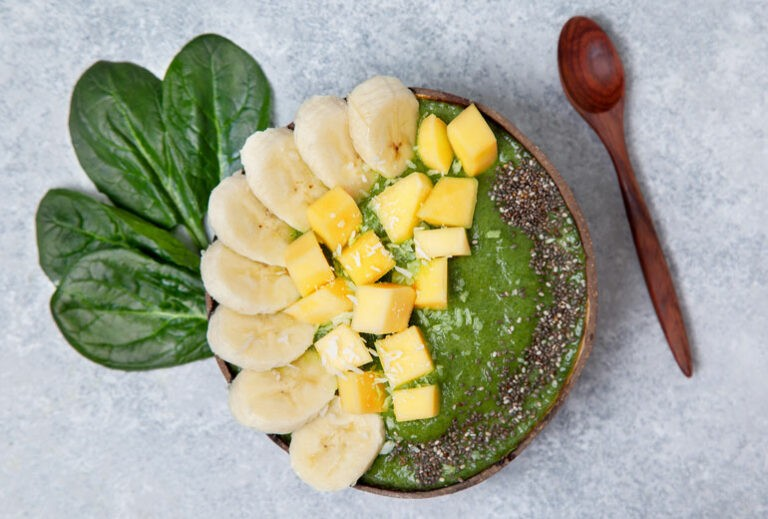 "a green smoothie in a wooden bowl with sprinkles of chia seeds and chunks of banana and mango next to spinach leaves and a wooden spoon on a gray slate background from Green Smoothie Girl's ""Smoothie Bowl"""